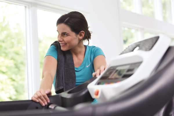 HZ15_LIFESTYLE_female ADVENTURE-3 treadmill leaning_console
