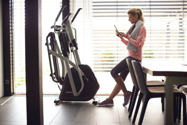 HZ14_LIFESTYLE_female andes 7i elliptical reading tablet_dining room